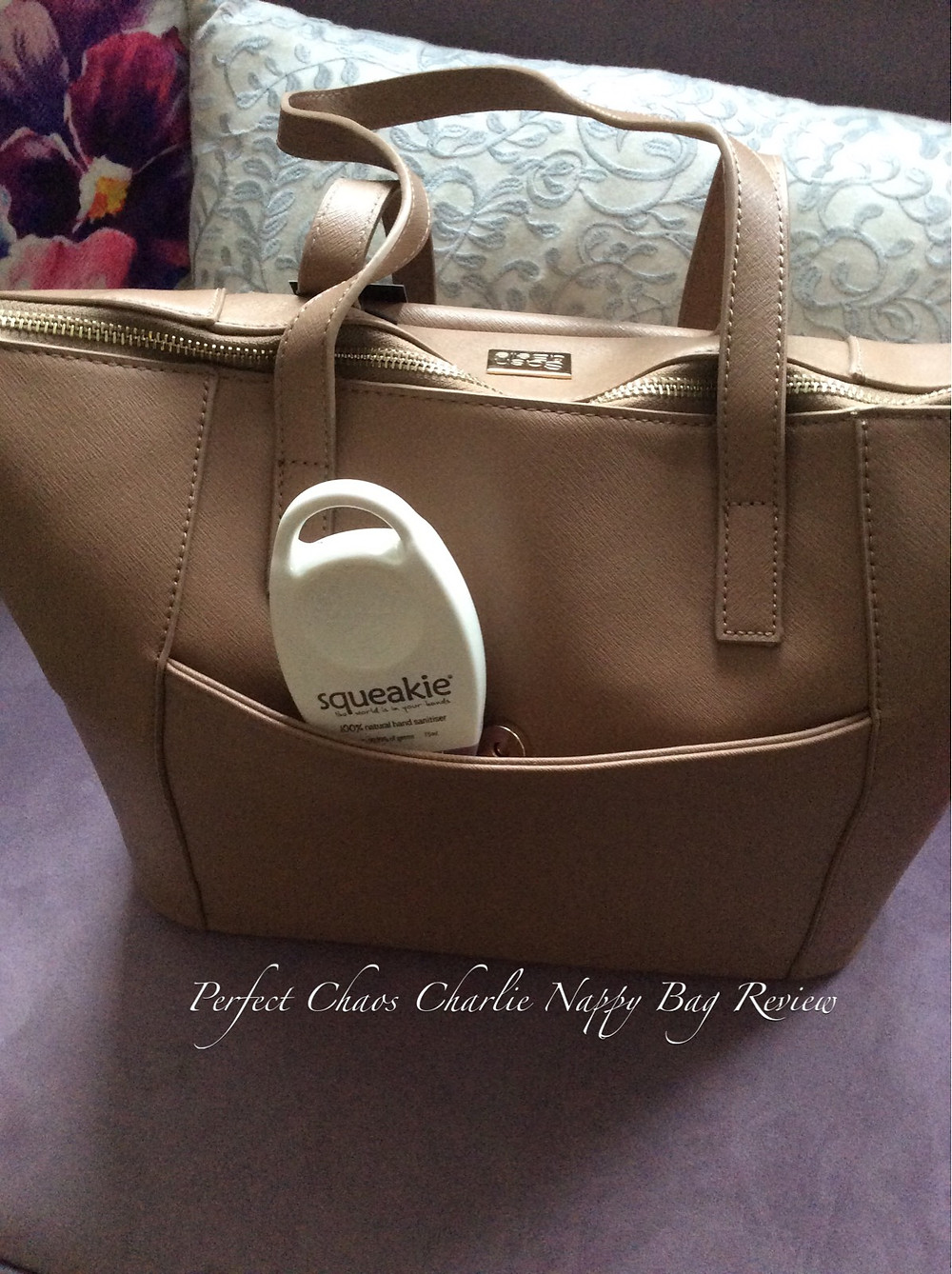 Rear view of the Sash & Belle Charlie Nappy Bag in Taupe with Squeakie 100% Natural Hand Sanitiser shown in rear pocket.