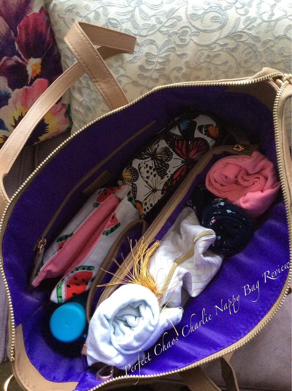 View of bright purple lining inside of a packed Sash & Belle Charlie nappy bag in taupe