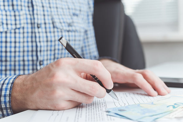 man-signing-contract-at-office-table-VF8