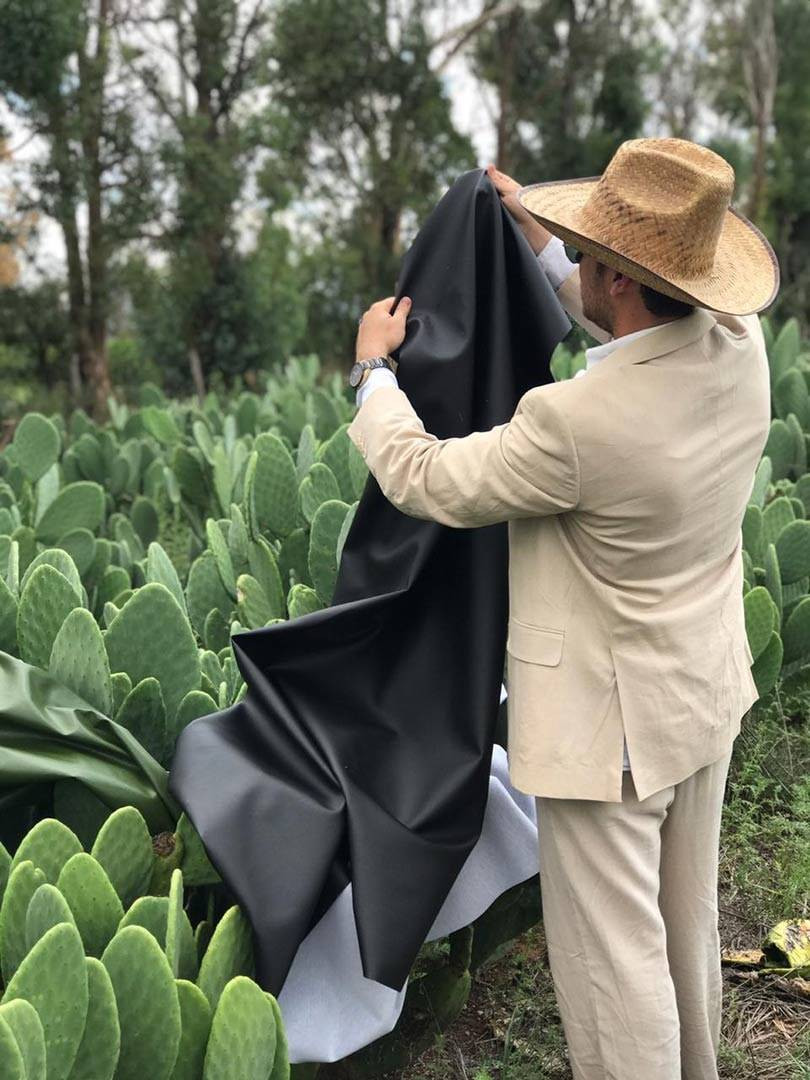 a man with a sun hat holds black desserto fabric made from cactus
