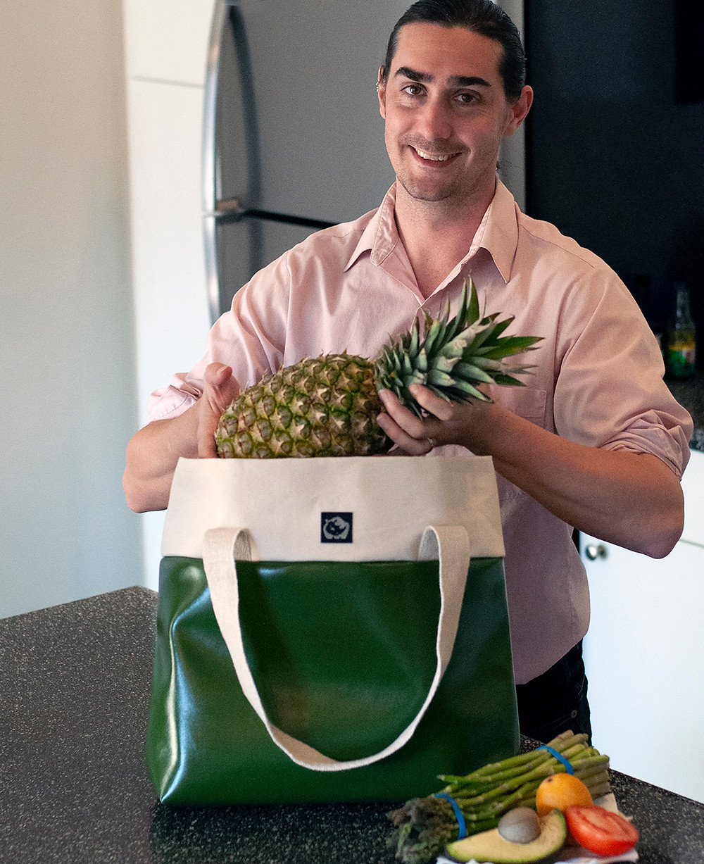 a man unpacks groceries from a shopping tote made with cactus leather, designer by White Rhino