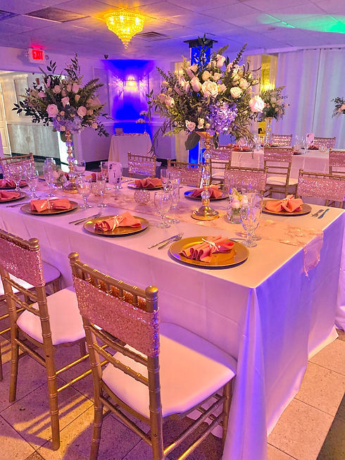 Table setup with floral arrangements, silverware, glassware, gold chargers, and gold chiavari chairs