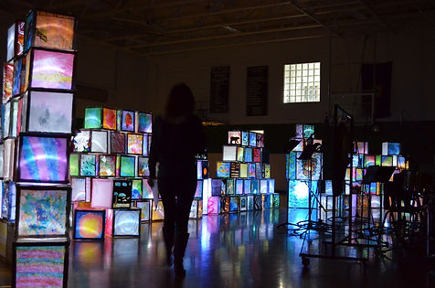 Stacks of hand painted cubes are lit up from within against a dark background