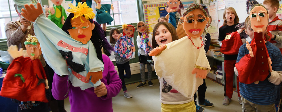Young students hold up puppets