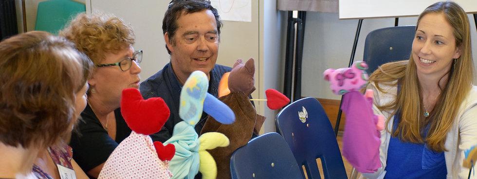 Educators sit holding puppets