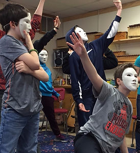 Students in theatrical poses wearing white masks