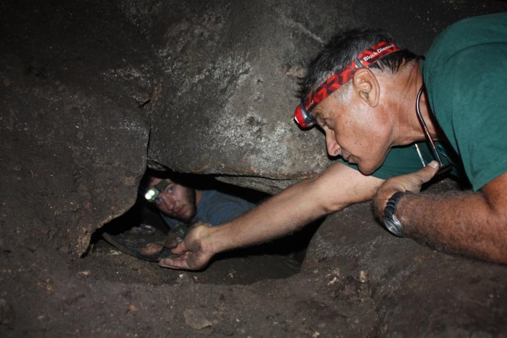 שמש יערן שולה נרות חרס ממקום הטמנתם מתחת לסלעים בולם המערה