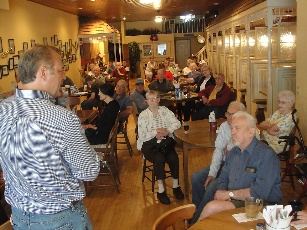 man speaking to audience in coffee shop