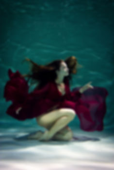 Dancing woman under the water in a pool