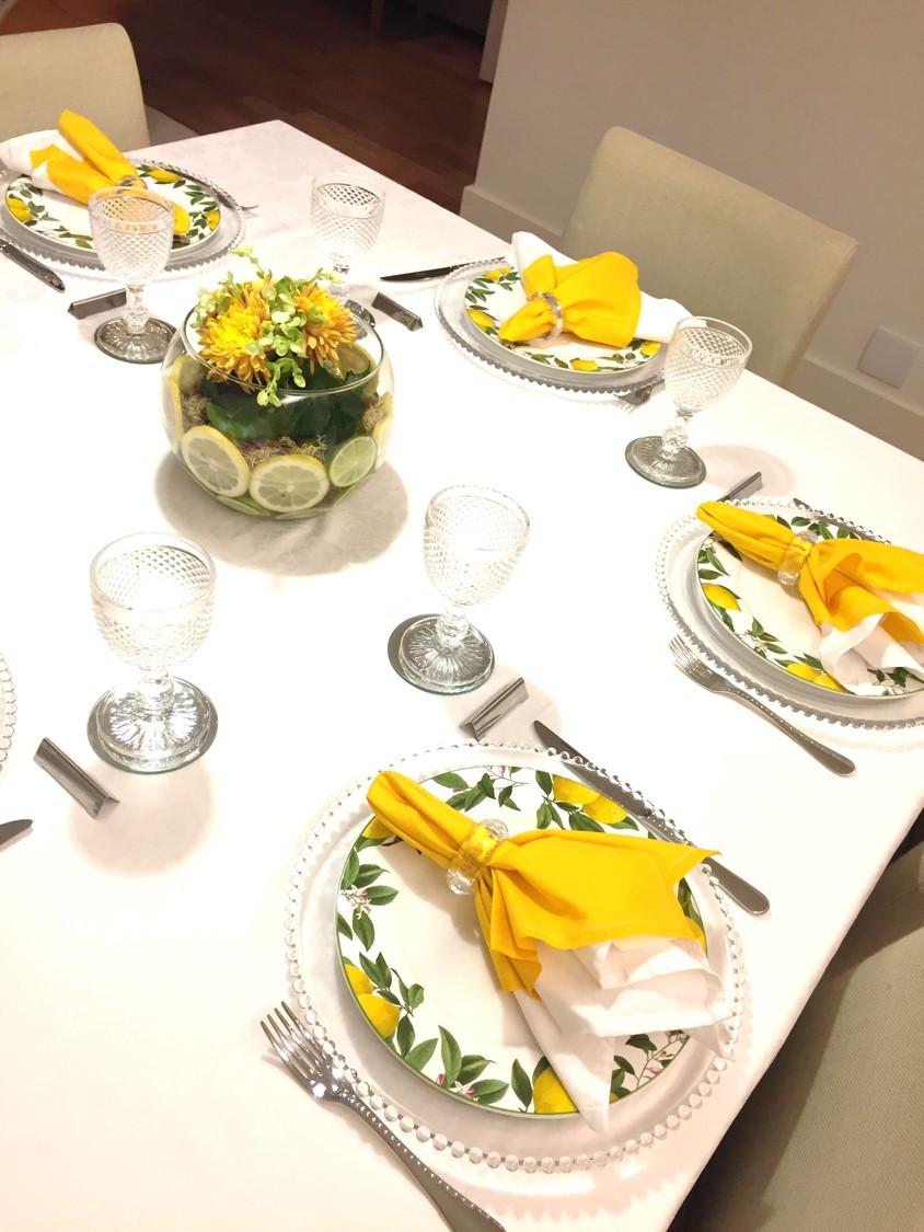 Mesa posta - jogo de pratos de limões sicilianos e arranjo de flores central em tons de amarelo