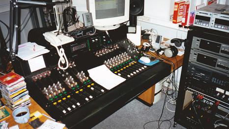 """Így nézett ki a stúdió péntek esténként: nagy halom CD, a pohárban kóla, és még egy kis """"hozzáadott érték...""""A monitoron az akkor épp fejlesztés alatt álló Nautilus adáslebonyolító látszik, meg egy csomó analóg cucc. A pulton balról jobbra haladva volt négy mikrofon, két telefonvonal, két CD, aztán jött a számítógép, DAT és Minidisc. Utóbbi a kép jobb felső sarkában látszik. A szignálokat mindig ezekről játszottam le."""