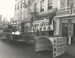 Hunan Garden restaurant, owned by San Wong,  installing a new sign, April 1976