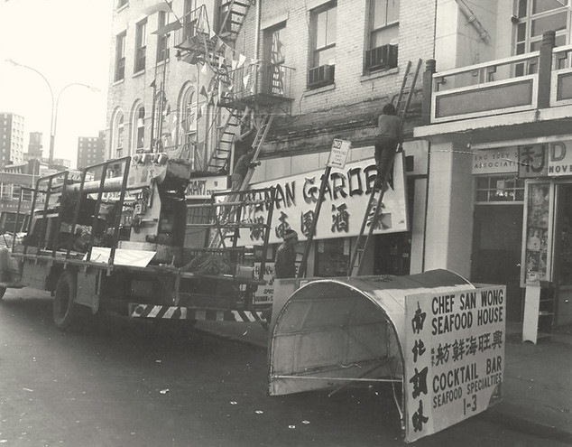 Hunan Garden restaurant, owned by San Wong,  installing a new sign. April 1976