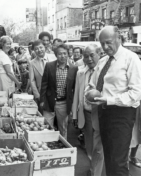 Mayor Koch holding a vegetable and looking confused while surrounded by onlookers