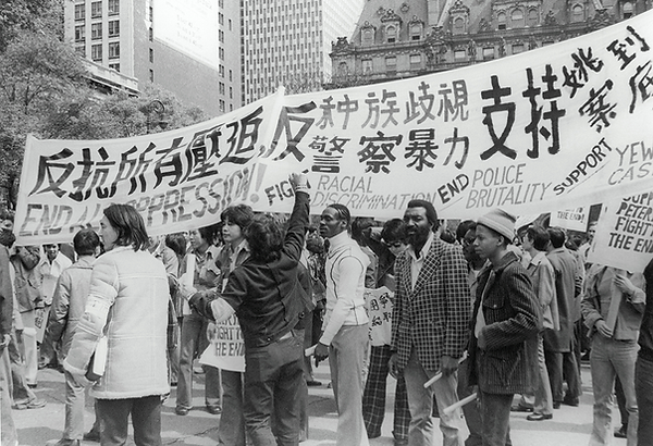 A multiracial group of protestor holding signs against racial discrimination, oppression, and police brutality in both english and chinese.