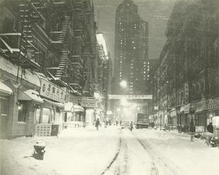 View of Bayard Street from Mott Street on a snowy night, date unknown