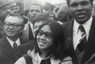 """Muhammad Ali with Linda J. Lee (center) and M.B. Lee (right), President of the Chinese Consolidated Benevolent Association, on """"Muhammad Ali Day,"""" December 9, 1974"""