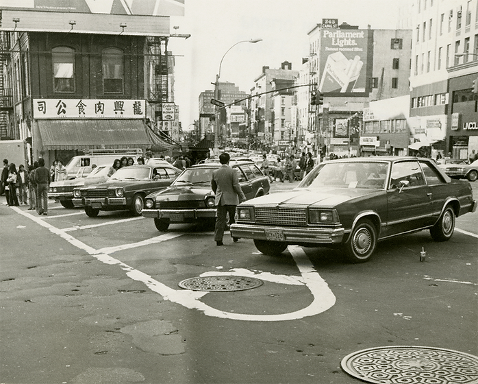 A very busy Canal Street at the Walker Triangle. The triangle is a parking lot for a group of 1970s sedans.