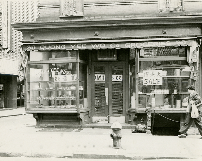 Quong Yee Wo Groceries storefront on the corner of Mott Street. The storefront looks as if it could be the 1930s
