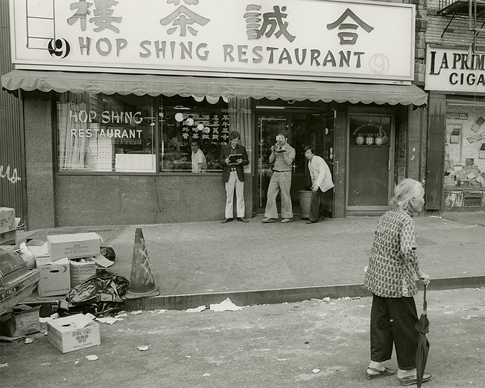Hop Shing storefront with a photographer and possibly a report out front.