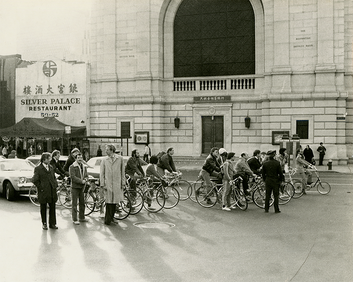 Cyclists lined up in front of the Manhattan Saving Bank across from the bass of the Manhattan Bridge. A two-story Chinese restaurant sits next door.