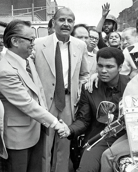 Muhammad Ali on the back of a motorcycle shaking hands with M.B. Lee during the parade