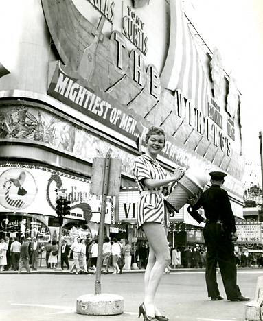 Teenage girl in a striped romper holding a extra-large prop Dariy Queen cone in Times Square.