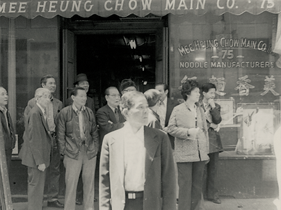 Parade gawkers standing infront of Mee Heung Chow Main Co. Noodle Manufacturers.