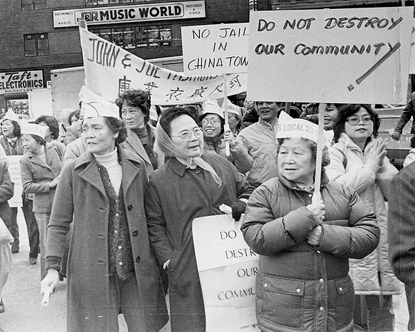 A large group of women wearing Local 23 hats protest the building of a Chinatown jail.