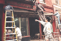 MOCA staff removing the fabric awning and sign from the Mee Heung Chow Main noodle company