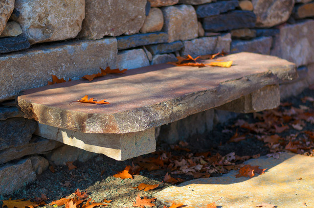 Redwood slab bench on cantilevered granite, dry laid stone wall