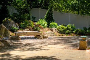 Japanese garden: Reclaimed granite stone bridge and dry stream with lighting, bluestone patio, stepping stone path, granite post and lantern, boulders and planting (design by Sallie Hill Design)