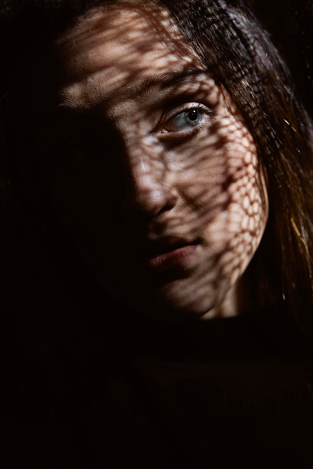 Studio portrait face lit through lace
