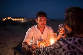 Romantic candlelit couple dining on beach