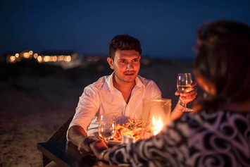 Romantic candlelit couple dining on beach