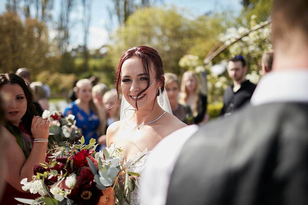 Wedding photography, bride over shoulder of groom in garden wedding