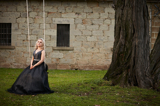 Outdoor portrait, girl on swing in lounge dress against stone wall