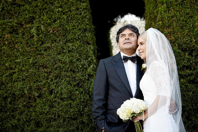 Wedding photography, classical portrait of bride and groom against highland hedge