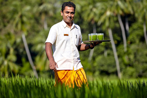 Smiling waiter carries herbal drink against jade green tropical background