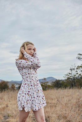 Outdoor portrait, girl in floral dress in burnt out field