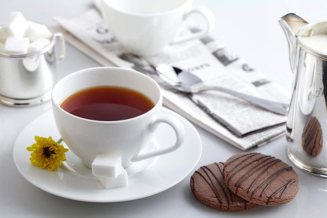 Food photography, cup of Ceylon Tea with biscuits and the daily newspaper