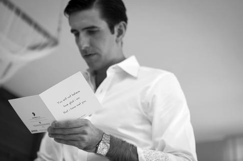 Wedding photography Tasmania, groom reads card from bride