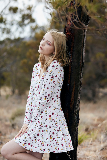 Outdoor portrait, girl in floral dress leans against burnt tree