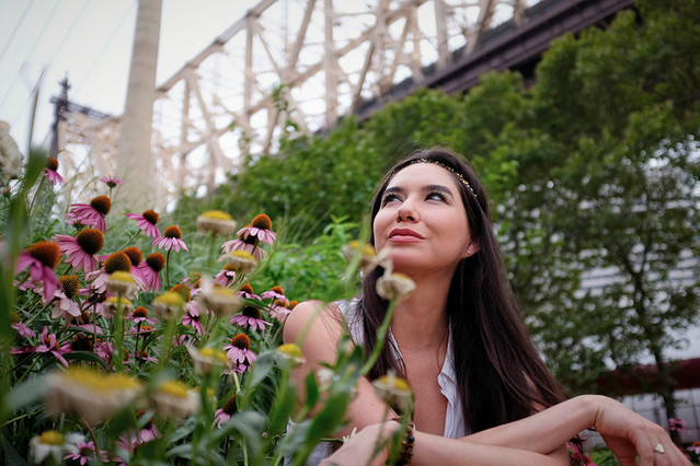 Outdoor portrait, girl in garden under a bridge in Manhattan
