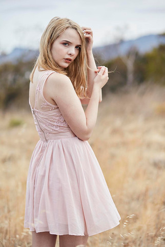 Outdoor portrait, girl in pretty pink dress in burnt out field