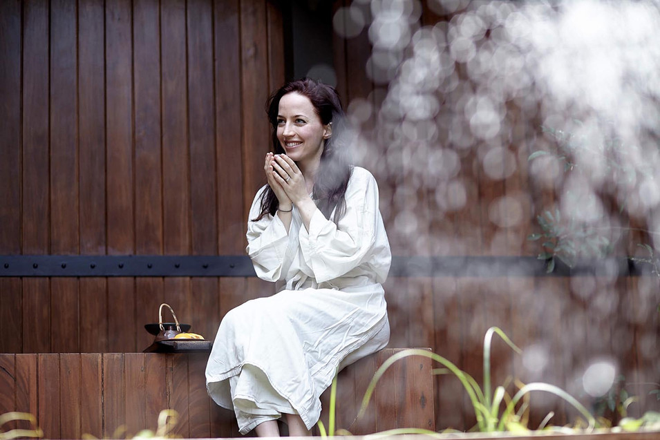 Leisure photography, woman in robe sips herbal tea outside a wooden spa