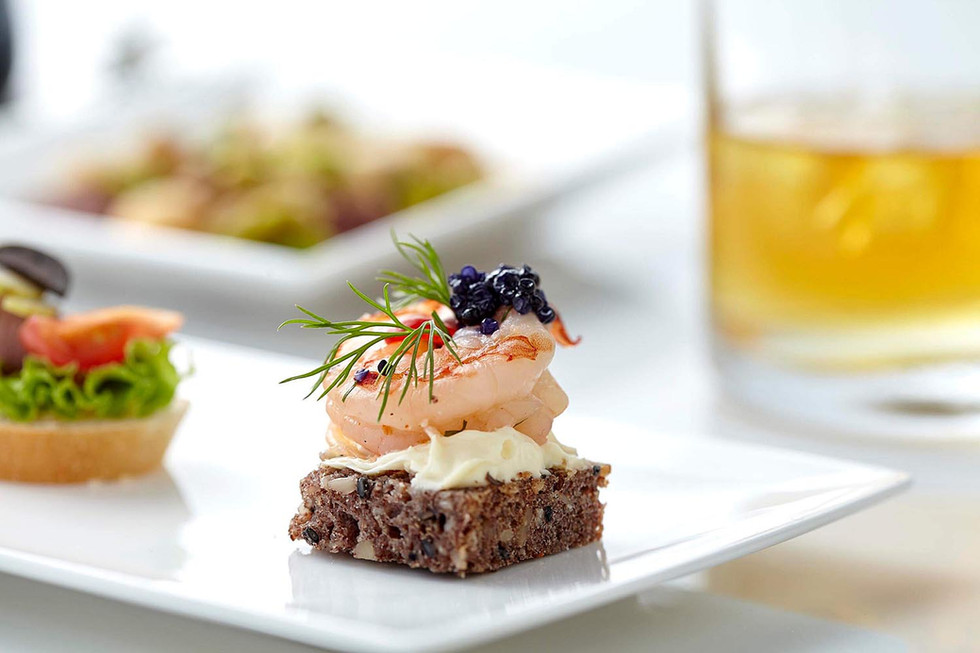 Food photography, prawn canapés with glass of whisky in the background