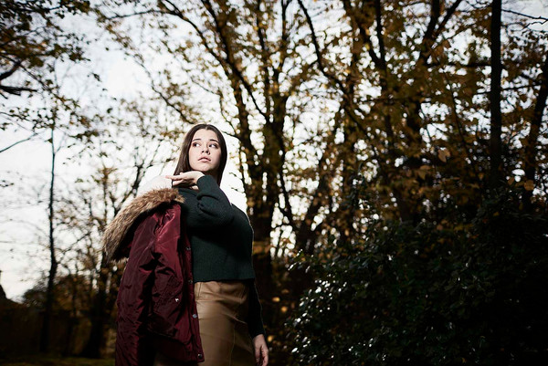 Outdoor portrait, girl in forest with jacket, late autumn light