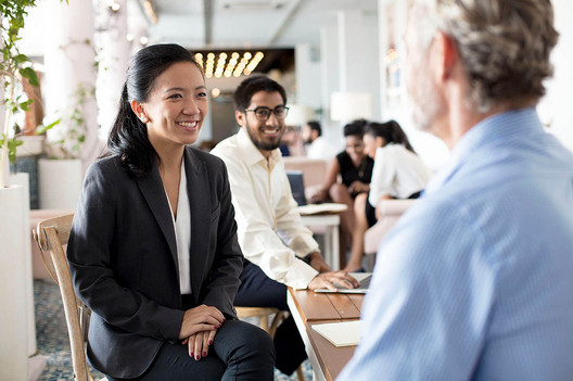 Commercial photography, business meeting asian girl speaks to white male