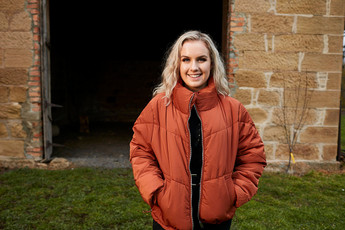 Lifestyle portrait, girl outside stone barn in burnt orange puffer jacket